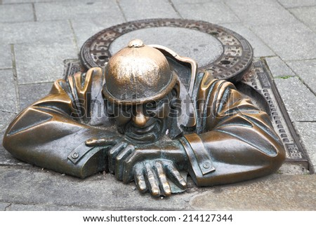 BRATISLAVA, SLOVAKIA - JUNE 25, 2014: Cumil (The Watcher) - famous statue of man peeking out from under a manhole cover. It was made in 1997 by Viktor Hulik #214127344