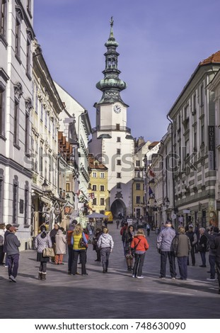 BRATISLAVA, SLOVAKIA - NOVEMBER 2, 2017: Tourists sightseeing on old street with famous St. Michaels watchtower