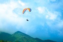 Brave and adventurous people fly on hang gliding wings
