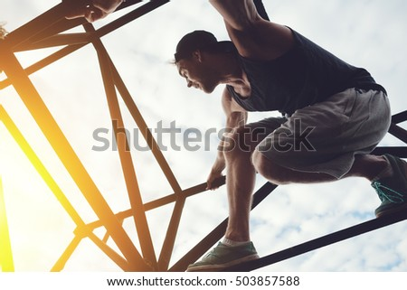Brave and risky man sitting on the top of high metal bridge