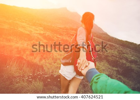 Brave and romantic adventure woman guiding man into the wild (intentional sun glare and vintage color)