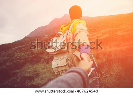 Brave and romantic traveler guiding woman to the mountain in the wild (intentional sun glare and vintage color)