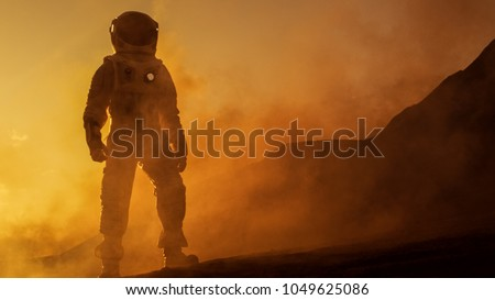 Brave Astronaut Confidently Walks on Mars Surface. Red Planet Covered in Gas and rock,  Overcoming Difficulties, Important Moment for the Human Race. #1049625086