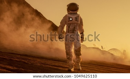 Brave Astronaut Confidently Walks on Mars Surface. Red Planet Covered in Gas and rock,  Overcoming Difficulties, Important Moment for the Human Race. #1049625110