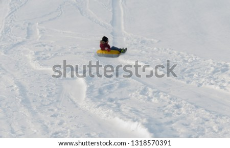 Brave child in red jackets, a trip in the winter from the mountains to tubing. He has an inflatable chamber. It slides quickly through the snow. #1318570391