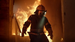 Brave Firefighter With Switched On Flashlight on His Helmet Runs Down the Burning Stairs. Fire is Raging.