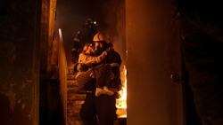 Brave Fireman Descends Stairs of a Burning Building with a Saved Girl in His Arms.
