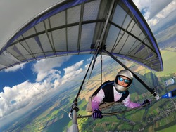 Brave girl hang glider pilot fly high above ground on a colorful purple hang glider. Wide angle action camera shot