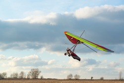 Brave girl learn to fly on the colorful hang glider wing. Extreme sport activity with beautiful sunset sky on the background. Mastering hang gliding
