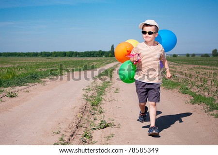 Brave little boy traveler walking the country road with bunch of colorful balloons in the sunny weather