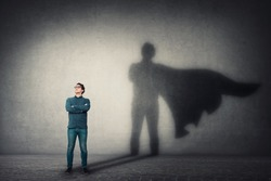 Brave man keeps arms crossed, looks confident, casting a superhero with cape shadow on the wall. Ambition and business success concept. Leadership hero power, motivation and inner strength symbol.