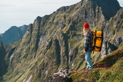 Brave man tourist climb on high mountains above sky. Hipster treveler wearing professional backpack standing alone on the edge cliff mountain and looking away. Adventure vacation