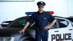 Brave policeman in service car and sunglasses posing on camera near patrol car