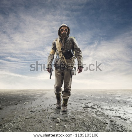 Brave soldier with gas mask and gun walking in a polluted post atomic landscape with toxic smog and clouds: environmental disaster and apocalypse concept