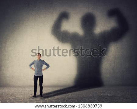Brave teenager boy facing his fears as a powerful hero. Guy casting a strong muscular bodybuilder shadow, showing big biceps. Self defense, inner strength and motivation and confidence concept. #1506830759