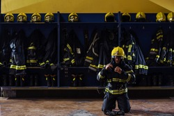 Brave young firefighter in protective uniform kneeling and putting on helmet on head and preparing for action. Fire station interior.