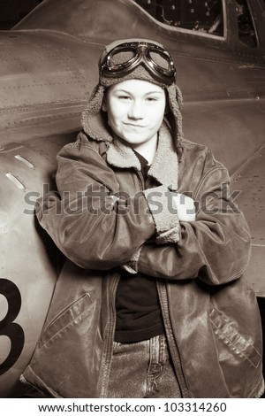 Brave young pilot resting against airplane, smirking at camera