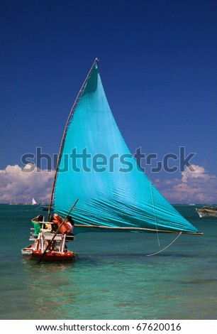 "Brazil Alagoas State Maceio traditional ""jangada"" raft with bright turquoise  sail adapted for tourism viewed from tropical beach"