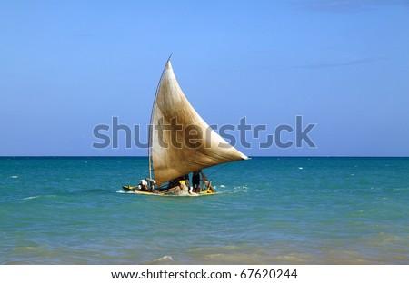 "Brazil Alagoas State Maceio traditional ""jangada"" wooden fishing raft sailing past a tropical beach"