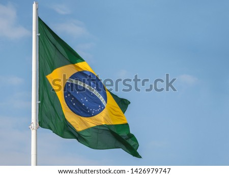 Brazil flag waving at the wind against blue sky #1426979747