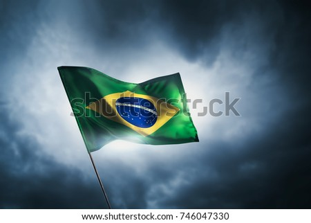 brazil flag waving with pride on a cloudy background / high contrast image #746047330