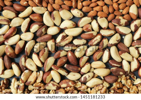 Brazil nuts, Almond nuts and walnuts are scattered evenly. Walnut background.