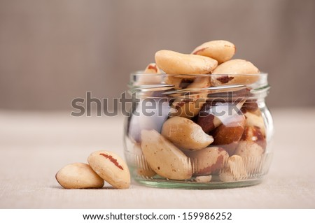 Brazil nuts from Bertholletia excelsa tree in glass jar and two nuts out of jar, healthy edible seeds food ingredient on table, blurred background, horizontal orientation, front view.