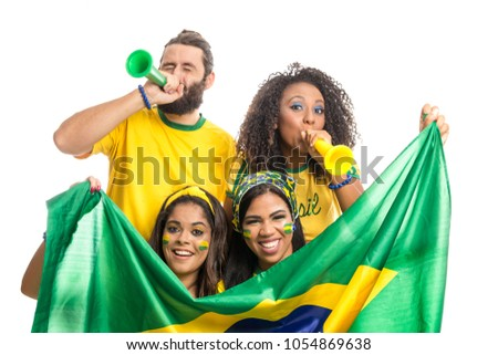 Brazil supporters. Brazilian group of fans celebrating on soccer / football match on white background. Brazil colors. Person is blowing a horn. Flag. #1054869638