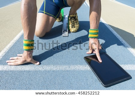 7e9f537292fe57 Brazilian athlete crouching at the starting line of a running track wearing  Brazil colors wristbands using