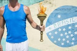 Brazilian athlete holding Olympic sport torch standing in front of a Brasil flag mural Rio de Janeiro Brazil