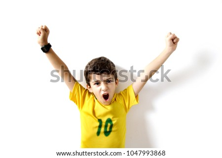 Brazilian boy, soccer player and fan, celebrates on white background. Hands up in the air. #1047993868
