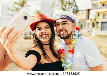 Brazilian Carnival. Couple in costume taking a self portrait #1305163525