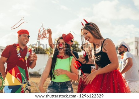 Brazilian Carnival. Group of Brazilian people in costume celebrating the carnival party in the city #1296122329