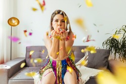 Brazilian Carnival. Young woman enjoying the carnival at home blowing confetti