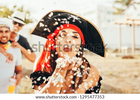 Brazilian Carnival. Young woman in costume enjoying the carnival party blowing confetti #1295477353