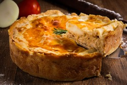 Brazilian Chicken Pie - Slice of a Homemade Chicken Pie on Spatula on a Wooden Table Rustic Appeal