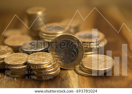 Brazilian coins and graphics. Economic indicators of Brazil. Selective focus and double exposure.