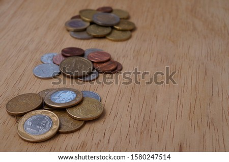 Brazilian coins, US coins and Euro coins on wooden background. #1580247514