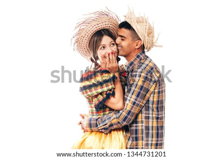 Brazilian couple wearing traditional clothes for Festa Junina - June festival - dancing isolated on white background