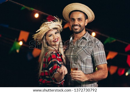 Brazilian couple wearing traditional clothes for Festa Junina - June festival - dancing under the night sky