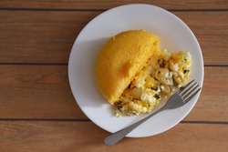 Brazilian couscous and scrambled eggs (Cuscuz com ovo) on wooden background. Typical Couscous of Northeast of Brazil.
