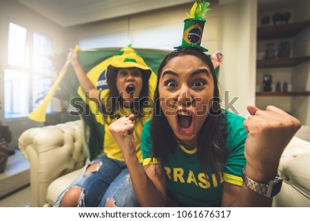 Brazilian fan celebrating during soccer match - Shutterstock ID 1061676317