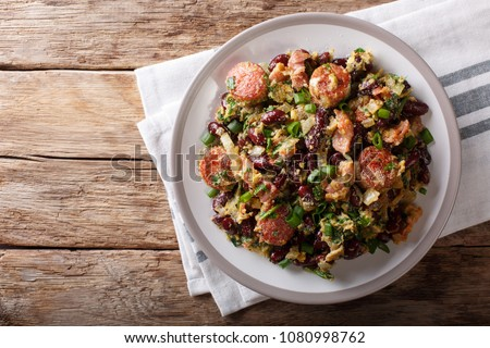 Brazilian Feijao Tropeiro traditional dish from Minas Gerais, made with beans, bacon, sausage, collard greens, eggs. horizontal top view from above