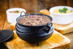 Brazilian Feijoada Food. Small, individual portion in an iron pan. small portion of feijoada, smoky and hot. Typical Brazilian food.