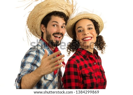 Brazilian Festa Junina. June party in Brazil. Beautiful couple wearing plaid clothes, traditional of the celebration. Man is inviting you to join in the party and the fun. #1384299869