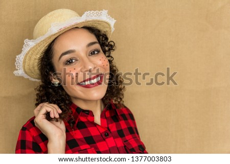 Brazilian Festa Junina. June party in Brazil. Pretty woman is having a big smile and looking at the camera. She wears red and black plaid shirt. The girl is wearing a straw hat. #1377003803
