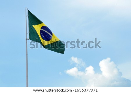 Brazilian flag flying and waving in the blue sky with nuves