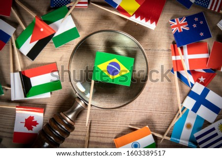 Brazilian flag. Politics, economics, imports and exports concept. Flags of many countries, magnifying glass on wooden table