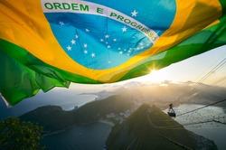 Brazilian flag shines above the golden sunset city skyline at Sugarloaf Pao de Acucar Mountain in Rio de Janeiro Brazil