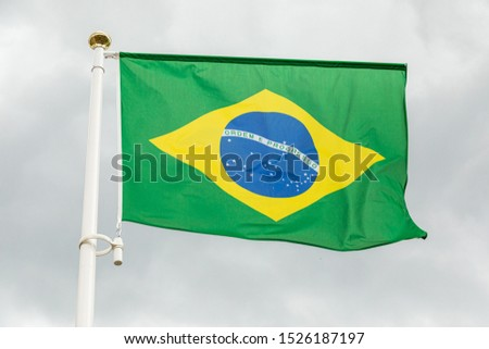 Brazilian flag waving in the wind against white cloudy sky